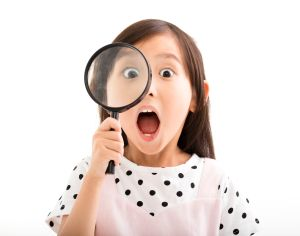 49363928 - little girl looking through a magnifying glass